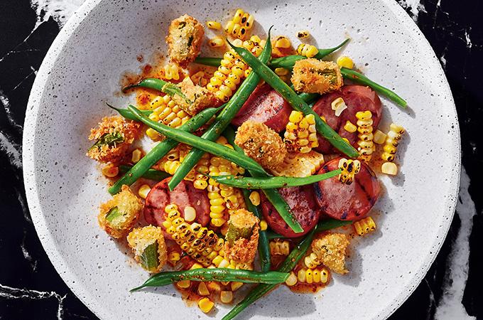 Salade cajun avec okras frits, maïs noircis, haricots et saucisse fumée